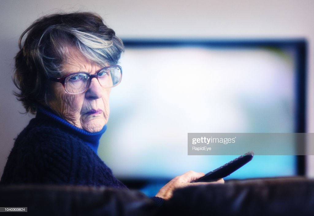 Old woman failing to master TV remote is frustrated : Stock Photo