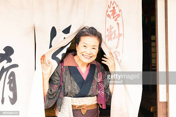 old woman greeting his customers in front of her shop - stereotypical homemaker stock pictures, royalty-free photos & images