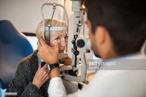 Old woman having an eye exam at ophthalmologist's office.