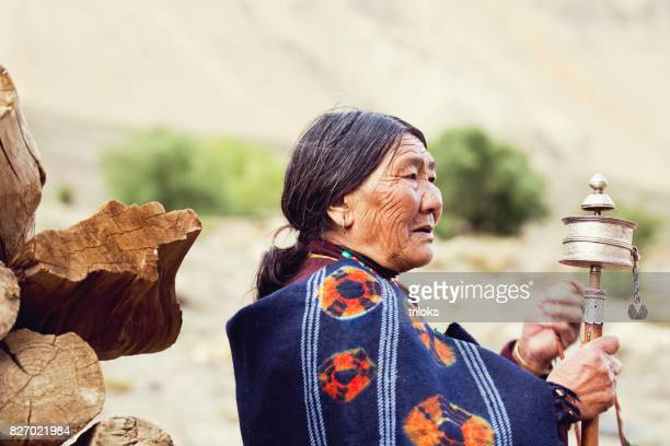 Old woman holding prayer wheel and beads