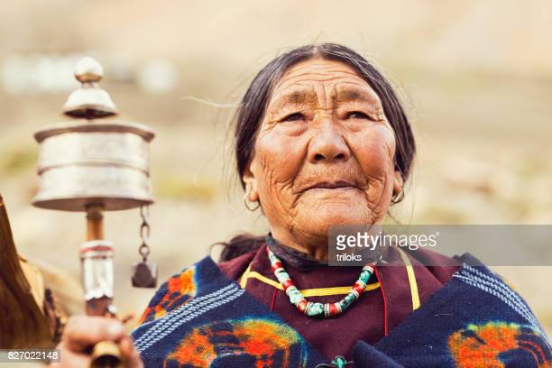 oude vrouw met gebedsmolen en kralen - himalaya stockfoto's en -beelden