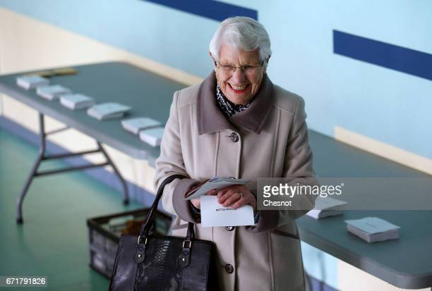 A old woman holds a French voter registration card and ballots during the first round of 2017 French presidential election at a polling station on...