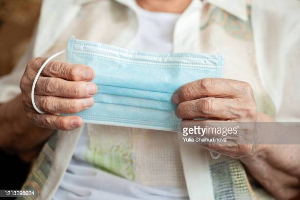 old woman holds medical mask in hands, blank table - senior women stock pictures, royalty-free photos & images