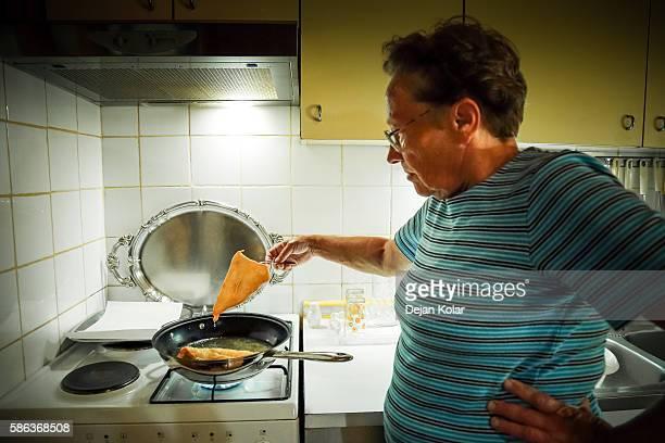 Old woman in kitchen, baking fresh dough in oil.