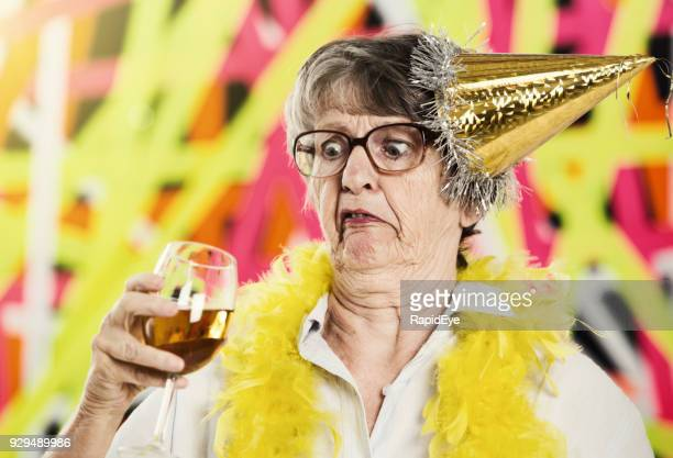 old woman in party hat looks at wine glass, horrified - old ugly woman stock photos and pictures