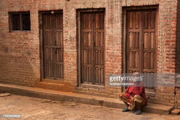 old woman in traditional red sari sitting in front of a newari style building in the changu narayan hindu temple complex in the kathmandu valley, nepal. this image was taken in 2016 and shows rubble and damage to buildings following the 2015 earthquake. - linda rama - fotografias e filmes do acervo