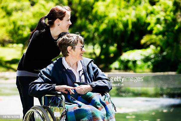 Old woman in wheelchair and teenager enjoy outing to park