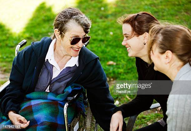old woman in wheelchair and two granddaughters laugh together - paraplegic woman stock photos and pictures