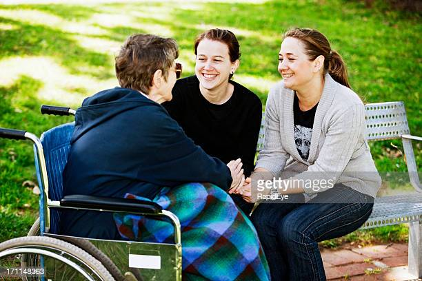 Old woman in wheelchair holds hands with smiling young women