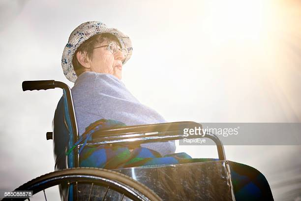 Old woman in wheelchair sits in the sun, looking hopeful