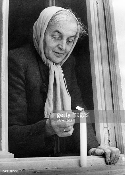 Old woman lights a candle which is placed in tn the window eraly fifties