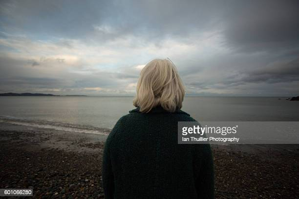 Old woman looking out at sea