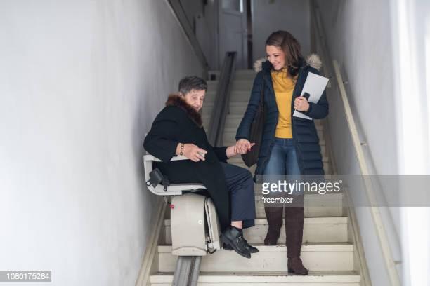 old woman moving down the stairs - elevador de escada imagens e fotografias de stock