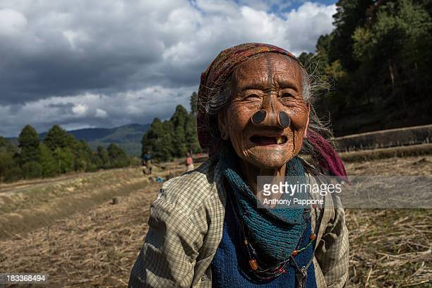 Old woman of the apatani tribe with nose pierced to work in the rice fields in ziro village, arunachel pradesh, india