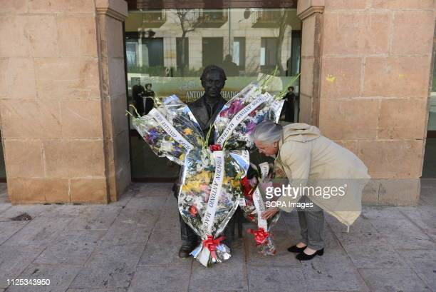 A old woman offer flowers before the statue of Spanish poet Antonio Machado in Soria north of Spain for the 80th anniversary of his death Antonio...
