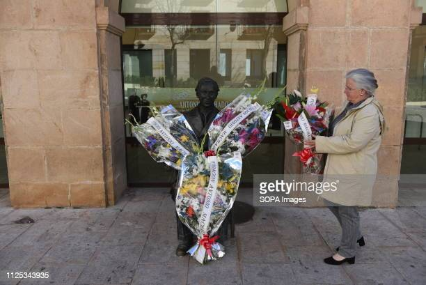 A old woman offers flowers before the statue of Spanish poet Antonio Machado in Soria north of Spain for the 80th anniversary of his death Antonio...
