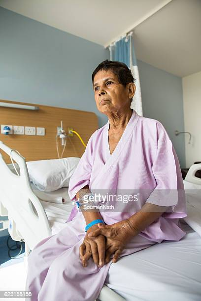 Old woman patient sitting on a Hospital bed