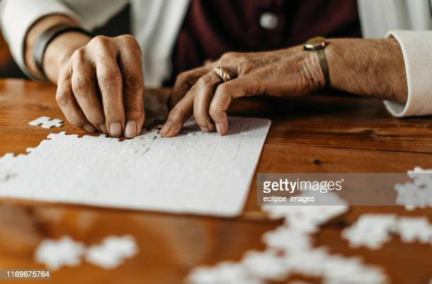 old woman playing puzzle game - puzzle stock pictures, royalty-free photos & images