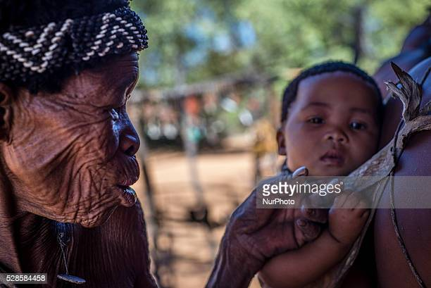Old woman plays with a baby in the Living Museum of the JuHoansiSan Grashoek Namibia