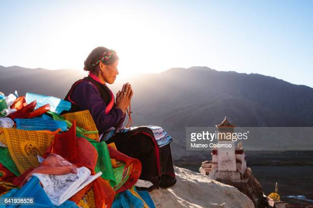 Old woman praying at sunset on top of hill, Tibet