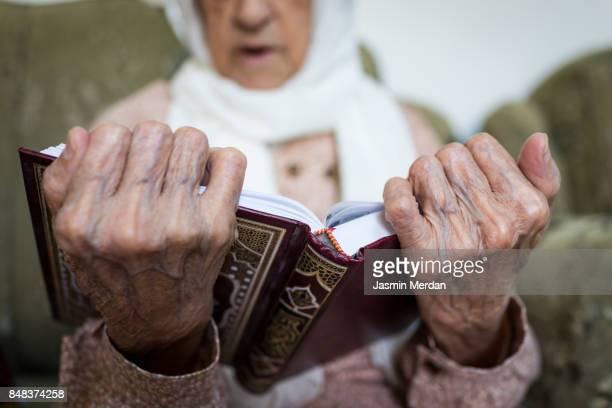 Old woman reading Koran