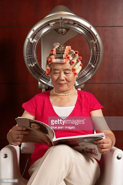 Old woman reading magazine under a hairdryer.