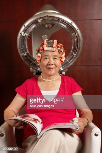 old woman reading magazine under a hairdryer stock photo