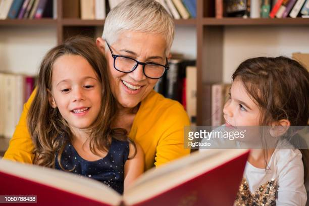 old woman reading to granddaughters - offspring stock pictures, royalty-free photos & images