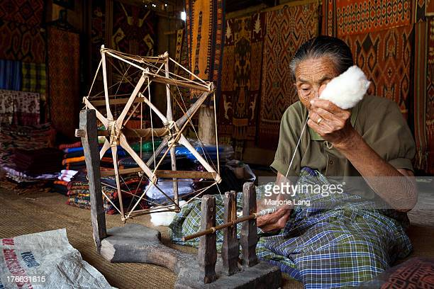 Old woman spinning cotton on a traditional wheel in Sa'Dan To Barana weaving village. Toraja countryside, south Sulawesi, Indonesia.