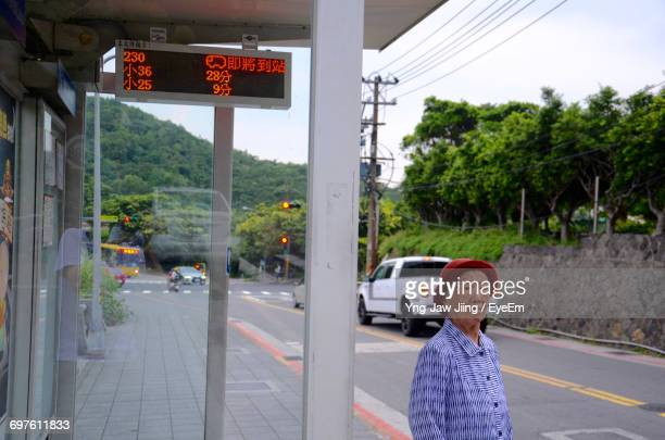 Old Woman Standing At Bus Station