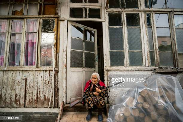 Old woman stands in the entrance of her home with a rifle during the shelling of the azeri army over Stepanakert city during the clashes between...