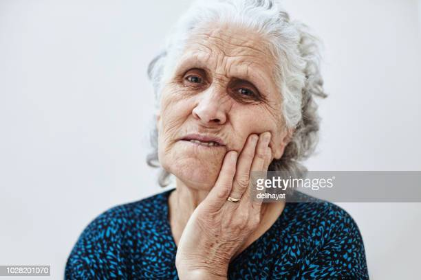 Old woman suffering because of toothache and is touching her cheek