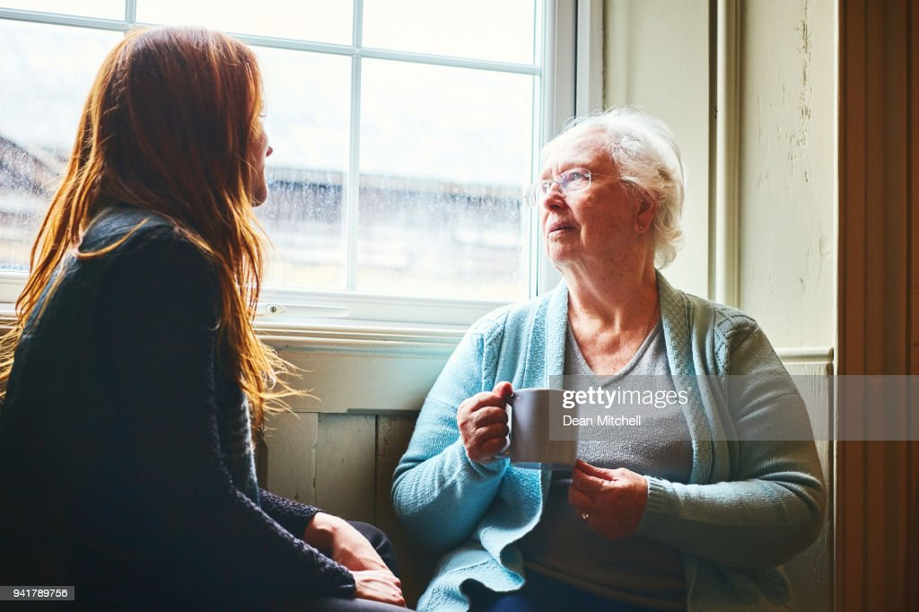Old woman talking with her young daughter at home : Stock Photo