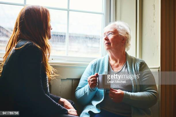 old woman talking with her young daughter at home - british granny stock photos and pictures