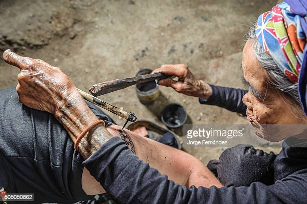 Old woman tattooing a tourist in a Philippine traditional way