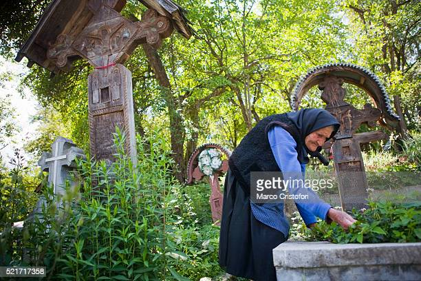 old woman tending a grave at lemn din deal church cemetery - marco cristofori fotografías e imágenes de stock