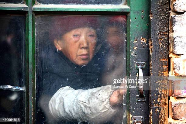 Old Woman Through the Glass Door in Winter - Wonderful people of Taiyuan, Shanxi Province, China
