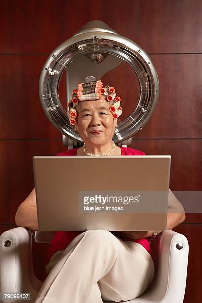 Old woman using laptop under a hairdryer.