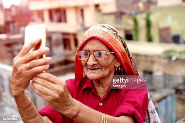 old woman using smart phone - developing countries stock photos and pictures