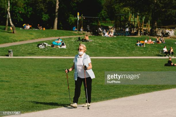 Old woman walks with face mask next to a re-opened playground after city relaxes its lockdown measure in Cologne, Germany on May 7, 2020.