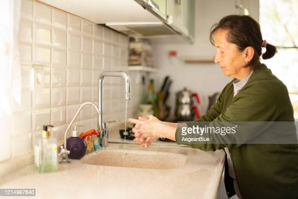 old woman washing her hand - covid icons stock pictures, royalty-free photos & images