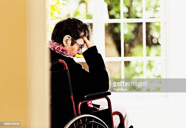 old woman, wheelchair bound with head in hands, is depressed - medische aandoening stockfoto's en -beelden