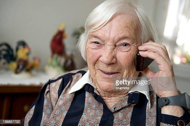 Alte Frau mit einem Mobiltelefon zu Hause fühlen