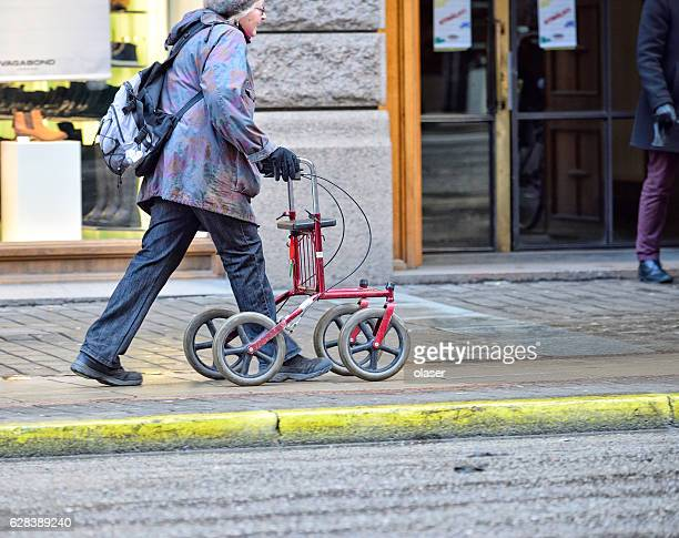 Old woman with walking support rollator on sidewalk