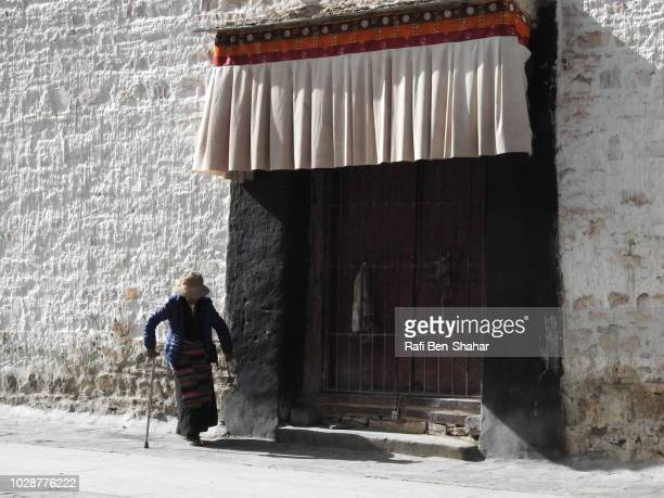 old woman worship in the entrance to the pelkhor chode temple - chode picture stock photos and pictures