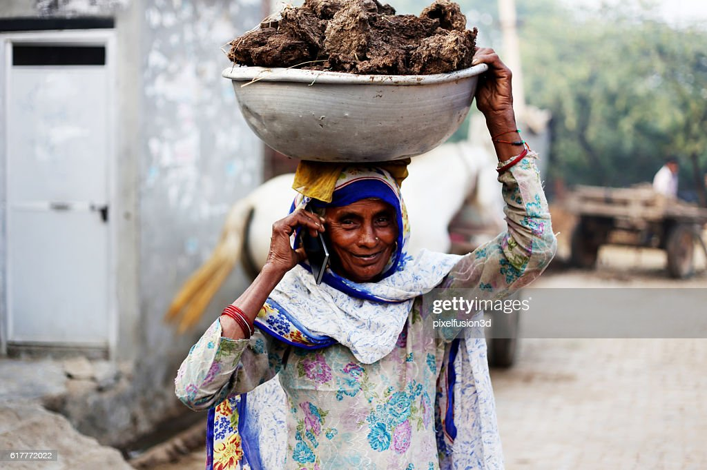Old women carrying cow dung and talking on phone : Stock Photo