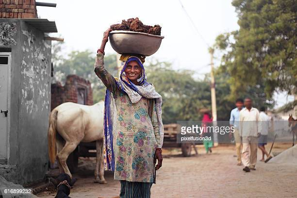 old women carrying cow dung - developing countries stock photos and pictures