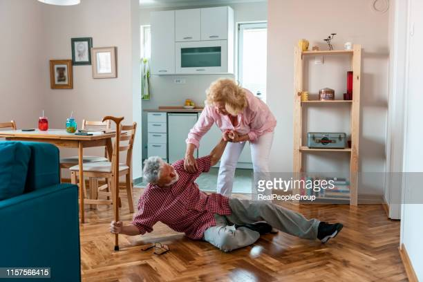 old women helping husband who falled down on floor - osteoporosis stock pictures, royalty-free photos & images