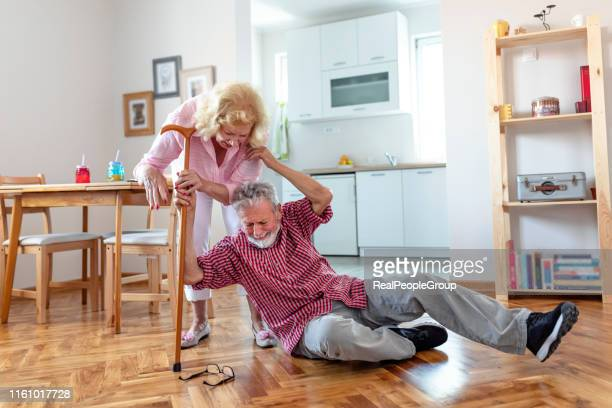 old women helping husband who falled down on floor - fragility stock pictures, royalty-free photos & images