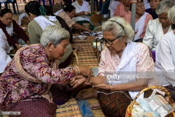 old women tying sacred threads. - tim bewer fotografías e imágenes de stock